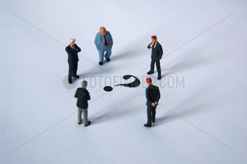 fuenf Managerfiguren stehen um ein Fragezeichen herum