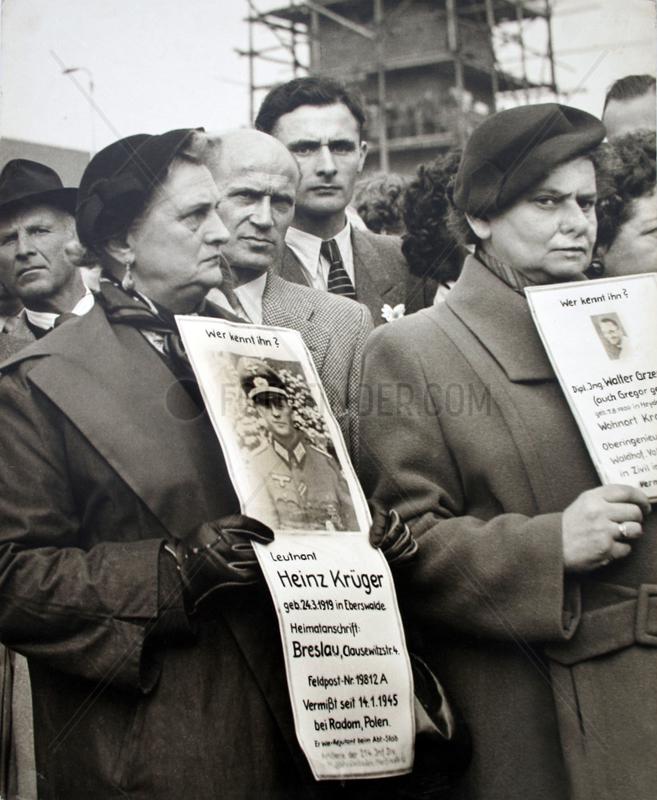 Frauen stehen und zeigen vermisste Maenner den Kriegsheimkehrern,  1955