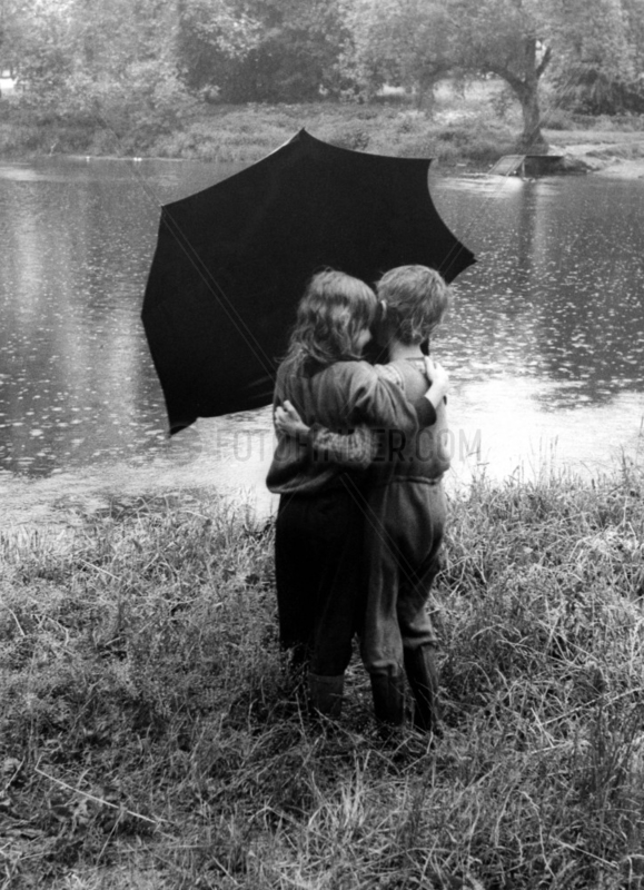 2 Kinder kuessen sich unterm Regenschirm