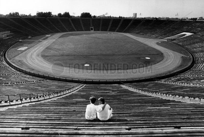 zwei Zuschauer in leerem Fussballstadion