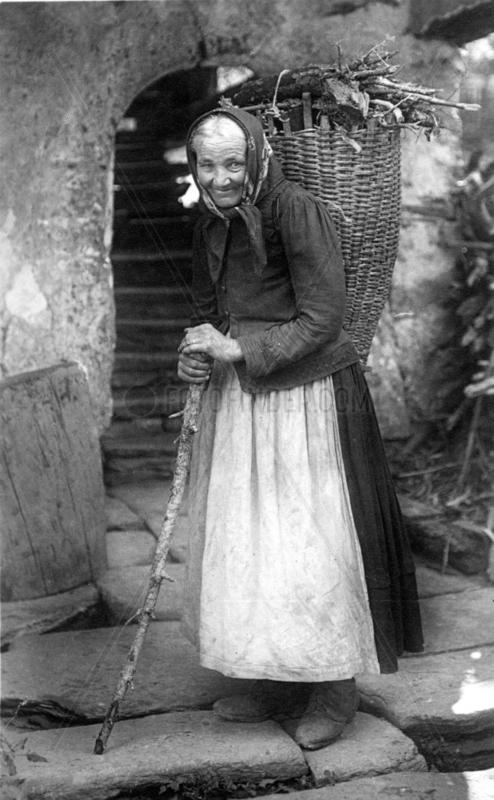 Alte Frau traegt Korb