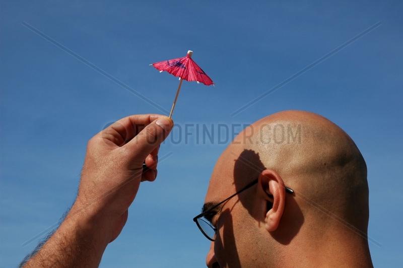 Mann mit kleinem Sonnenschirm