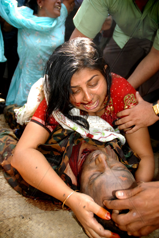 A woman cries holding her relative's dead body