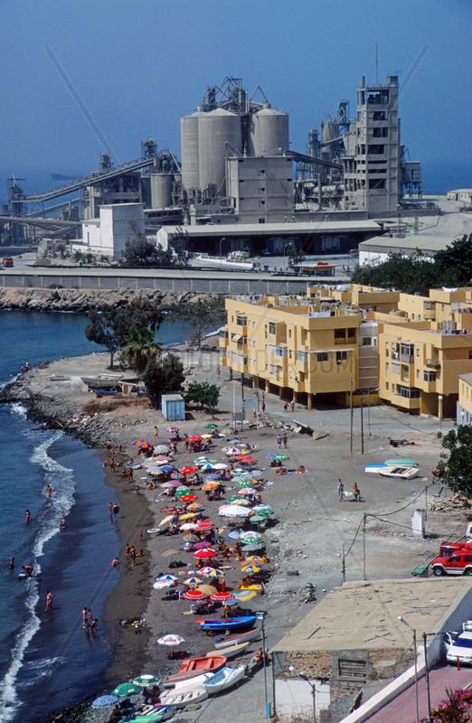 Badegaeste entspannen am Strand neben einer Industrieanlage,  Spanien,  Gran Canaria