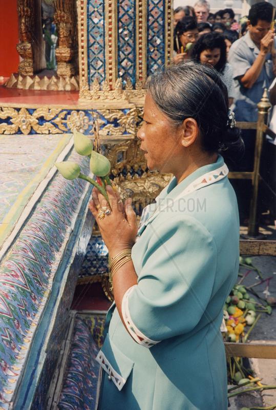 Thailand,  Bangkok,  Wat Phra Kaeo,  betende Buddhistin mit Lotusbluete