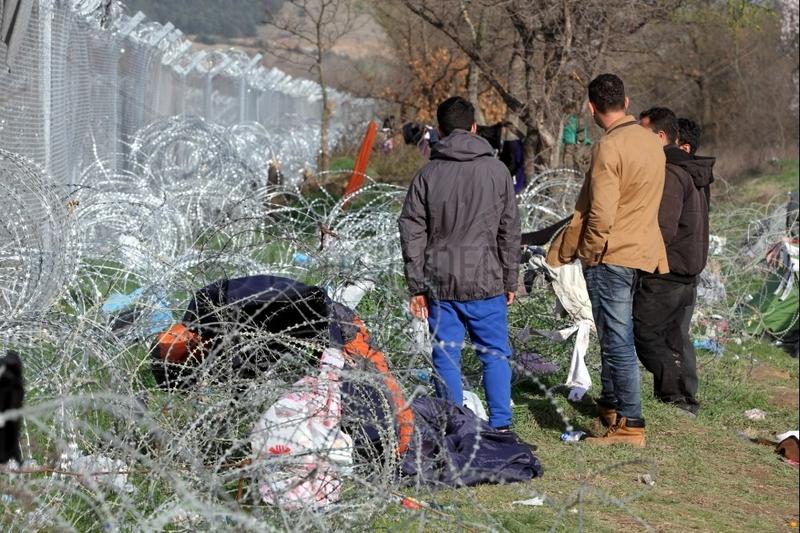 Fluechtlinge auf der Balkanroute vor einem Grenzzaun
