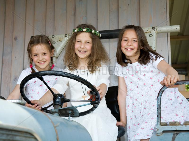 Riedlingen,  Deutschland,  drei Maedchen auf einem Traktor