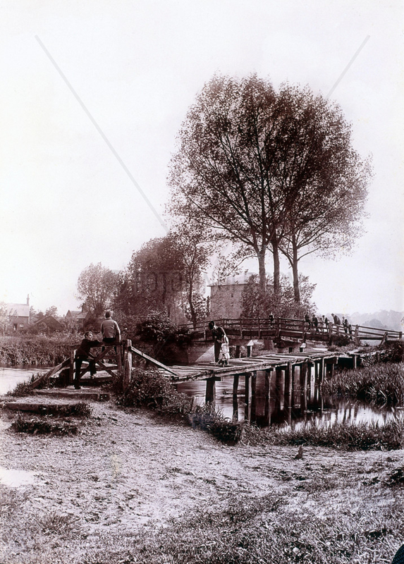 Adults and children on a wooden bridge over