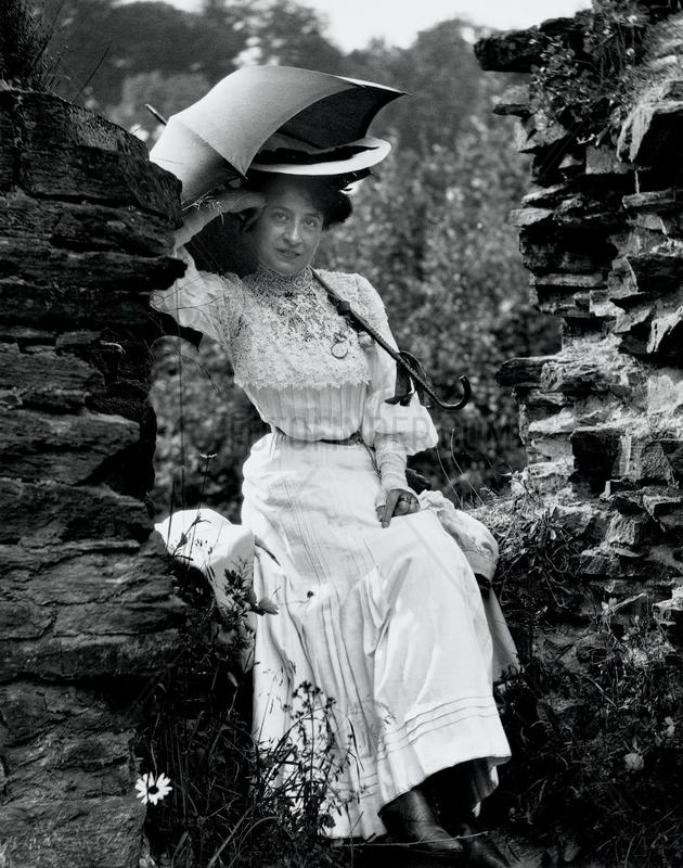 Edwardian woman sitting on a wall,  c 1900s.