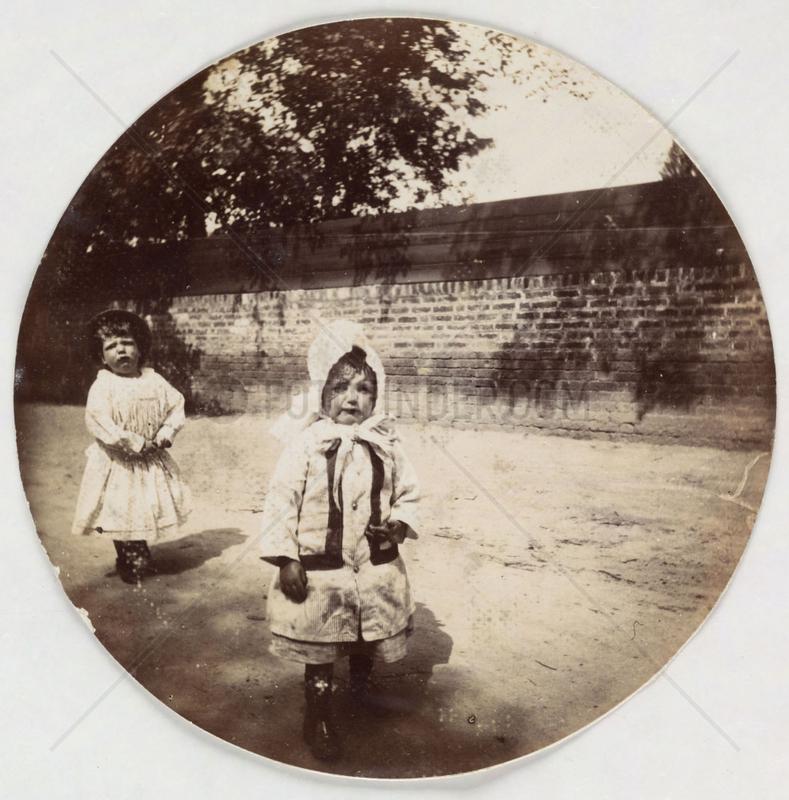 Two small children walking alongside a wall,  c 1890s.