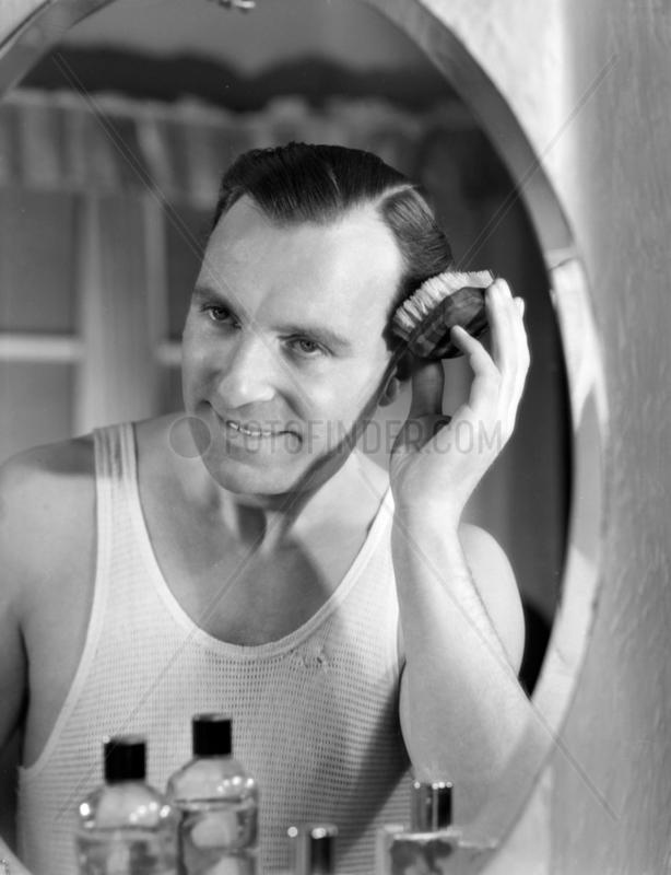 Man brushing his hair,  c 1945.