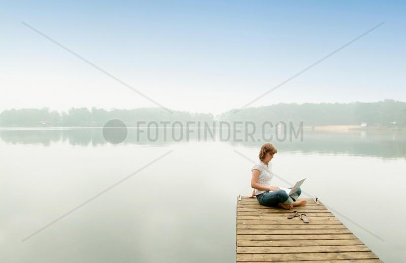Steg; Frau; 18; 19; 20; 22; 25; Jahre; jung; morgen; Nebel; neblig; Holzsteg; sitzen; Laptop; See; Wasser; Anlegestelle; alleine; Einsamkeit; Schleier; barfuss; Arbeit; arbeiten; Auszeit; Freizeit; bewoelkt; clouds; cloudy; cloudy skies; cloudy sky; commun