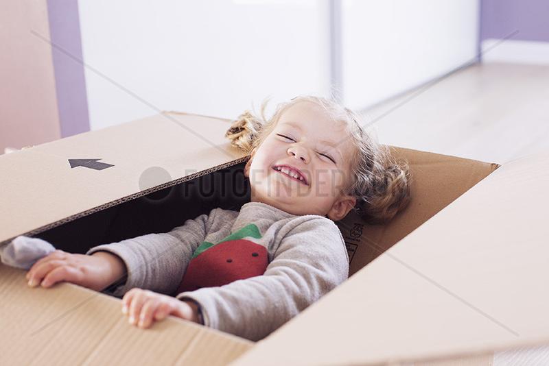 Little girl playing in cardboard box,  portrait