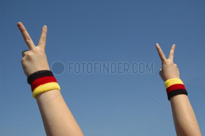 zwei Haende mit Victoriazeichen und Pulsbaendern in den Deutschlandfarben