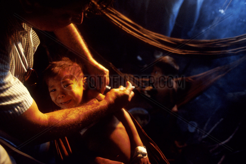 Christian Missionary at work caring for underfeeded Yanomami ( Ianomammi ) Indigenous child with malaria in Amazon rainforest,  Brazil. Physician. Surucucus region; State: Roraima; Amazon rainforest; North Brazil.