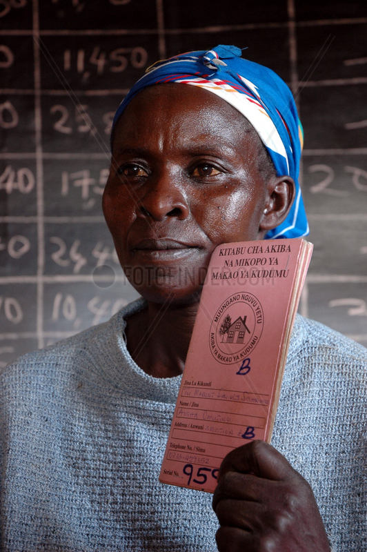 Eunice Atieno,  a petty trader in Toi Market shows her saving book within the sprawling Kibera slums in Nairobi November 23,  2006. Over three thousand petty traders with no formal training in small bussineses trading have come together and are raising more