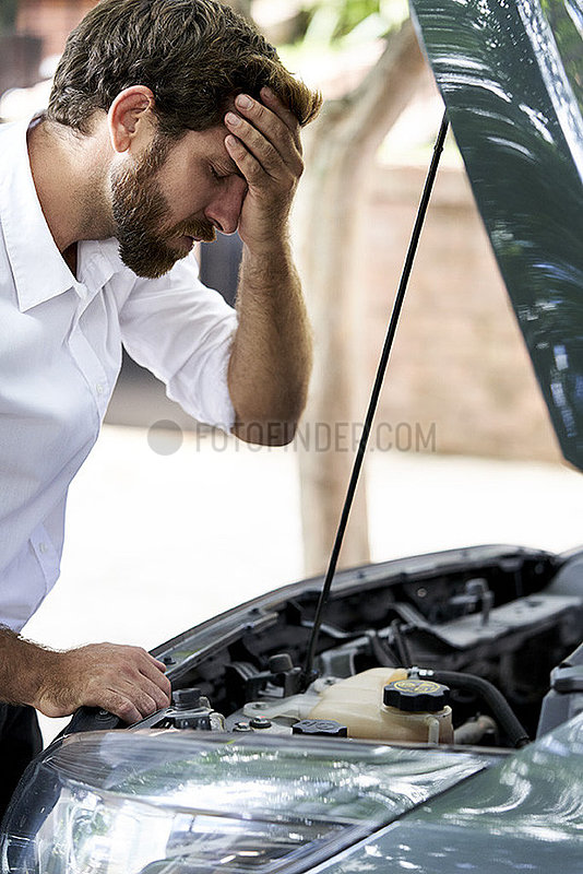 Frustrated man standing by car