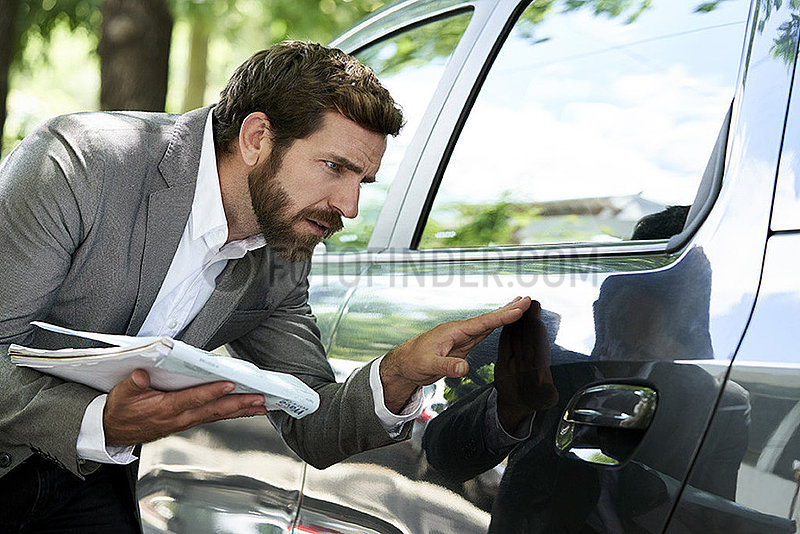 Salesman examining car