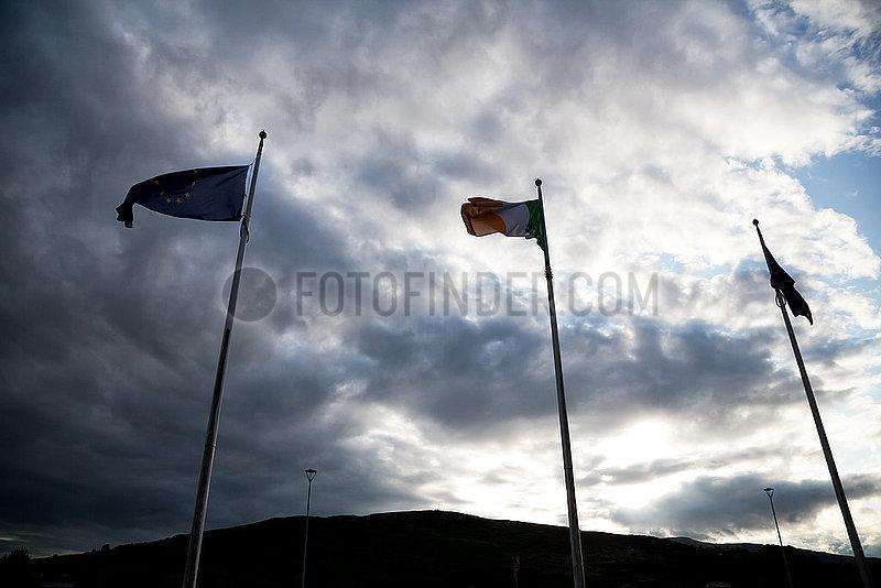 Irland,  Dundalk - Irische Grenze: Irische Fahne eingerahmt von zwei EU-Fahnen,  die Berge gehoeren zu Nordirland