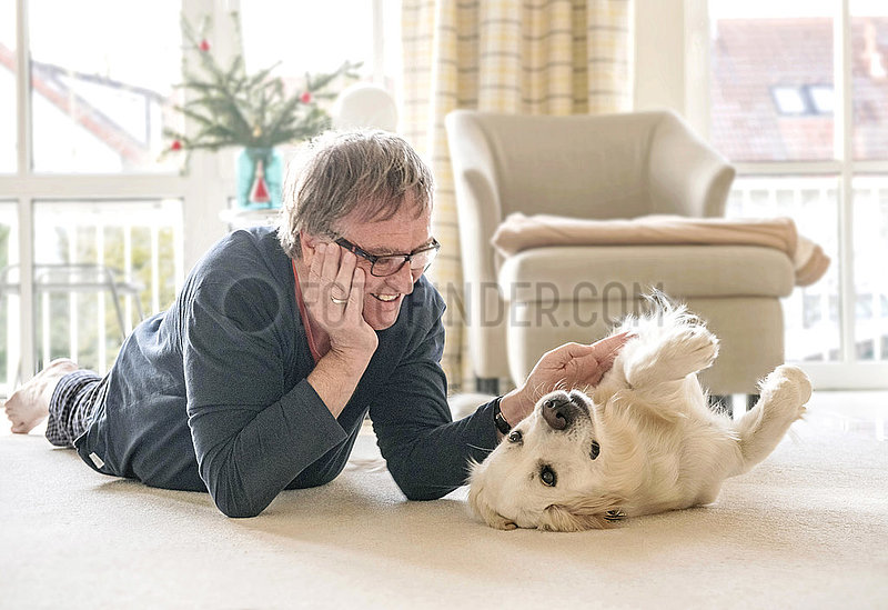 Mann spielt zuhause mit Retriever