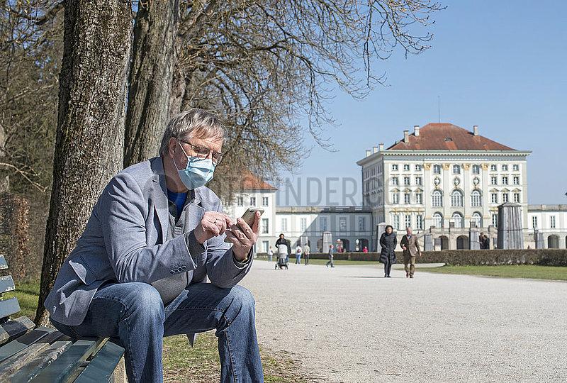 aelterer Mann mit Munschutz,  Nymphenburger Schlosspark,  Muenchen,  April 2020