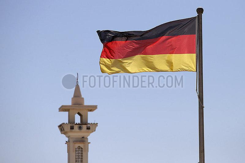 Doha,  Katar,  Nationalfahne der Bundesrepublik Deutschland weht vor einem Minarett