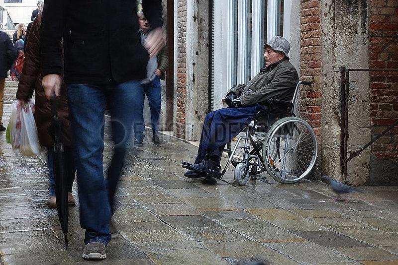 Venedig,  Italien,  alter Mann sitzt im Rollstuhl von Passanten ignoriert auf einer Strasse