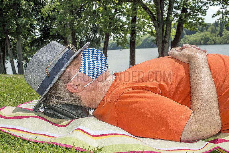 Mann mit Mundschutz,  schlaeft im Gras,  Urlaub in Bayern,  Juni 2020