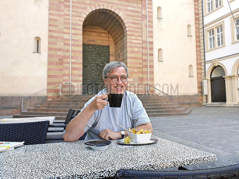 Mann beim Sonntagsfruehstueck vor dem Dom,  Wuerzburg,  Juli 2020