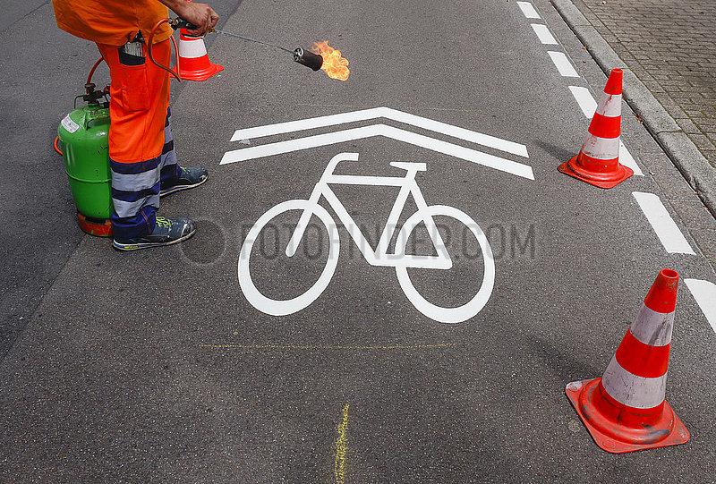 Neue Fahrradstrasse,  ein Fahrbahnmarkierer beim Aufbringen der Fahrrad Piktogramme,  Essen,  Ruhrgebiet,  Nordrhein-Westfalen,  Deutschland