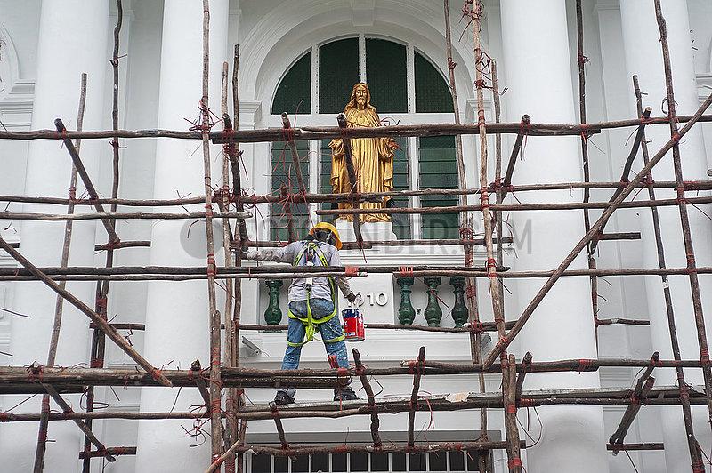 Singapur,  Republik Singapur,  Arbeiter mit Farbeimer steht auf dem hoelzernen Baugeruest einer Baustelle
