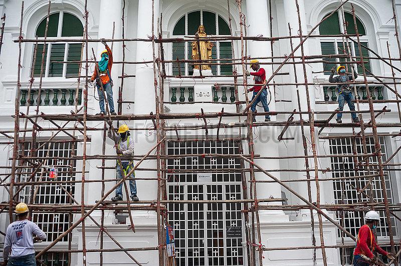 Singapur,  Republik Singapur,  Arbeiter bauen auf einer Baustelle ein hoelzernes Baugeruest ab