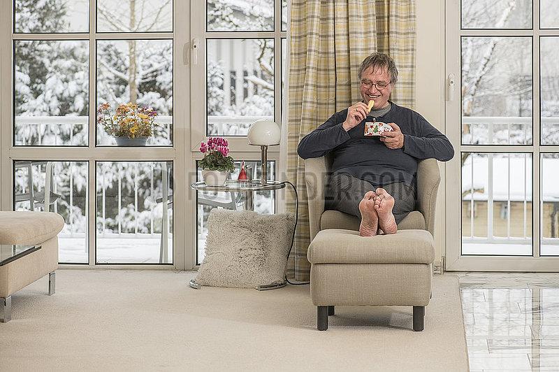 Mann im Lockdown zu Hause,  Plaetzchen essen,  Muenchen,  Januar 2021