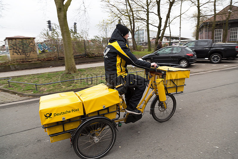 Deutschland,  Hamburg - Postbote auf seiner Tour mit einem Elektrofahrrad