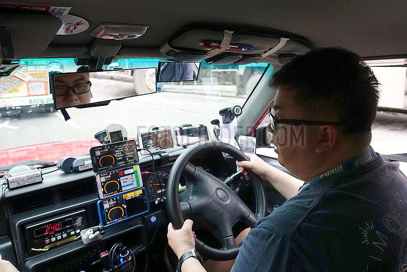 Hong Kong,  China,  Taxifahrer hat zahlreiche Smartphones an seinem Armaturenbrett