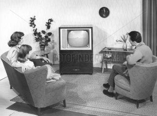 Modellfamilie in Modellwohnzimmer vor Fernsehgeraet