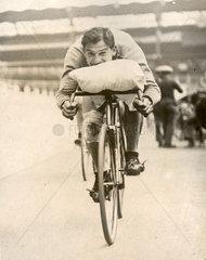 Mann auf Rennrad mit Kissen auf dem Lenker