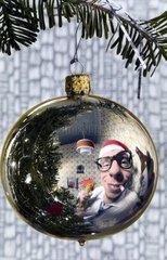 Mann spiegelt sich in Weihnachtskugel