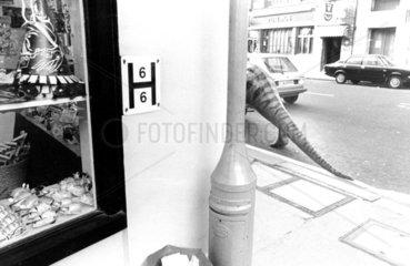 Dino verschwindet hinter Ecke  Strasse