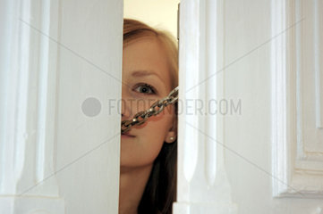 Frau schaut durch den Tuerschlitz
