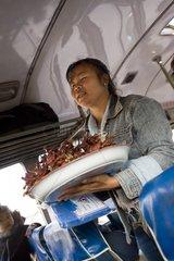 Laotin verkauft rohes Fleisch als Proviant im Bus von Vientiane nach Savann