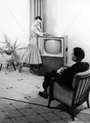 Frau posiert vor Fernsehapparat - Mann sitzt im Sessel