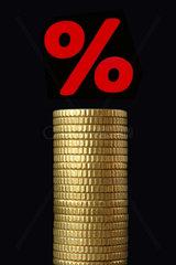 Prozentzeichen ueber Stapel aus Muenzen