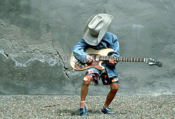 Junge als Cowboy spielt Gitarre