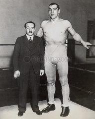 Mann in Anzug posiert mit riesigem Boxer