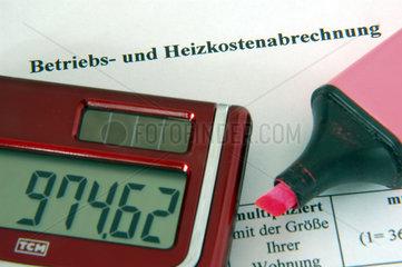Taschenrechner und Rotstift auf einer Betriebskostenabrechnung