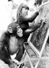Maedchen und Affe schreiben auf Tafel
