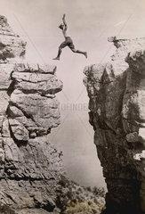 Mann springt _ber Schlucht zwischen zwei Felsen