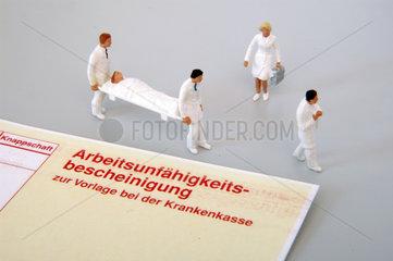 Medizinerfiguren neben einer Arbeitsunfaehigkeitsbescheinigung