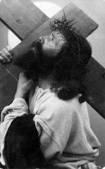Jesus Christus mit Dornenkranz traegt Kreuz